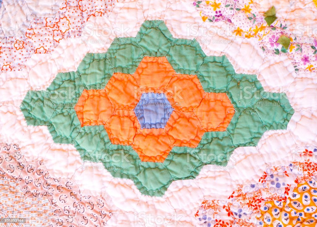 Vintage American quilt detail in green, orange, and pink.