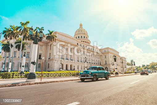 A vintage American retro car rides on an asphalt road in front of the Capitol in old Havana. Tourist taxi. paseo del prado, de mart