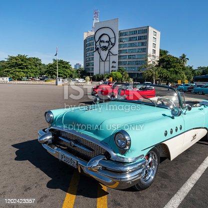 November 27, 2019, Havana, Cuba: Vintage American retro cars stands on revolution square on the background portrait of Camilo Cienfuegos