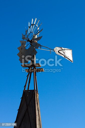A vintage American windmill against a deep blue sky. Copy space available.