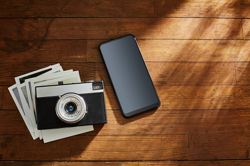 Vintage analog 35mm film camera, some photographs and a smart phone on wooden table under afternoon sunlight
