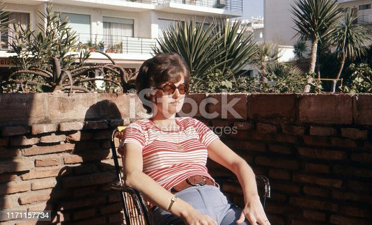 1974 vintage analog image of a young pregnant woman enjoying the sun on her balcony in Torremolinos, Spain.
