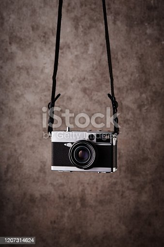 Vintage analog rangefinder film camera hanging in front of a concrete textured wall as background
