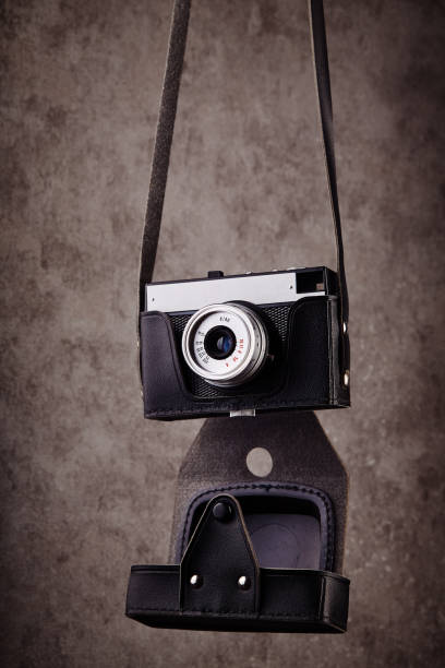 Vintage analog rangefinder film camera in leather case hanging in front of a concrete textured wall as background stock photo