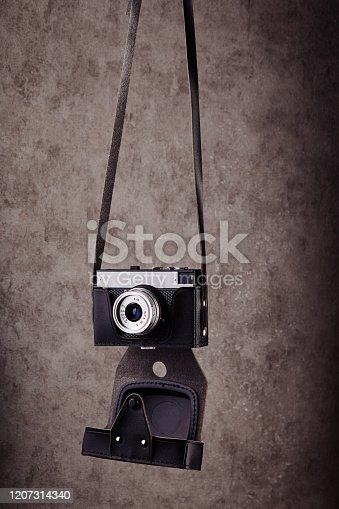 Vintage analog rangefinder film camera in leather case hanging in front of a concrete textured wall as background