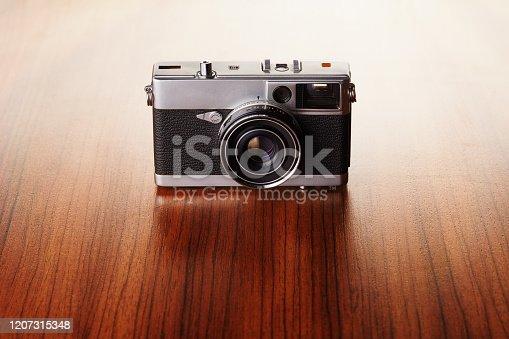 Vintage analog rangefinder film camera on wooden table