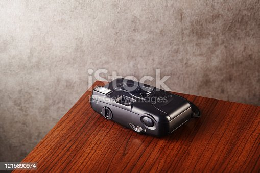 Vintage analog rangefinder film camera on wooden table with concrete textured wall as background