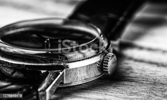 A vintage analog wristwatch with crown in black and white