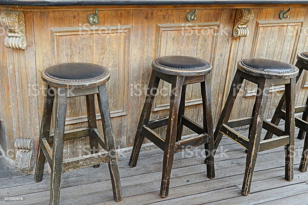 Vintage and rustic wooden bar stools on wooden floor stock photo