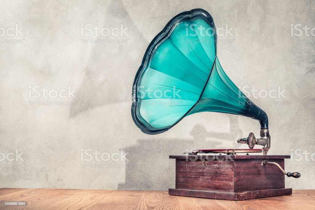 Vintage antique aged aquamarine gramophone phonograph turntable on wooden table front concrete wall background with its shadow. Retro old style filtered photo stock photo