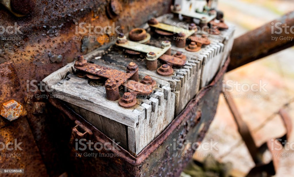 Vintage antique automotive wooden ignition coils covered in orange rust and age stock photo
