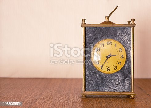 671883446istockphoto vintage antique classic mechanical clock made of black marble stone with golden dial on wooden shelf. front close-up view 1168055554