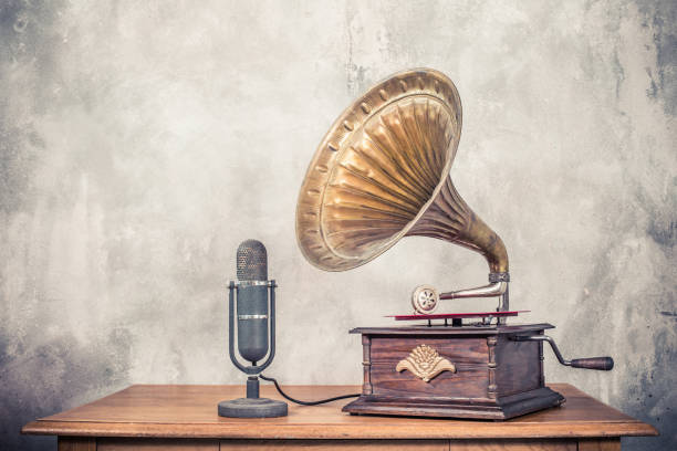 vintage antique gramophone phonograph turntable with brass horn and big aged studio microphone on wooden table front concrete wall background. retro old style filtered photo - 1940s style stock pictures, royalty-free photos & images