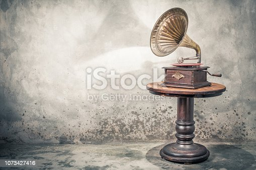 Vintage antique gramophone phonograph turntable with brass horn and red color vinyl disc record on wooden table front concrete wall background with shadow. Retro old style filtered photo