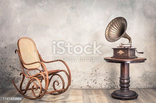 istock Vintage antique gramophone phonograph turntable with brass horn on wooden table and aged rocking chair front concrete wall background with shadow. Retro old style filtered photo 1141433864
