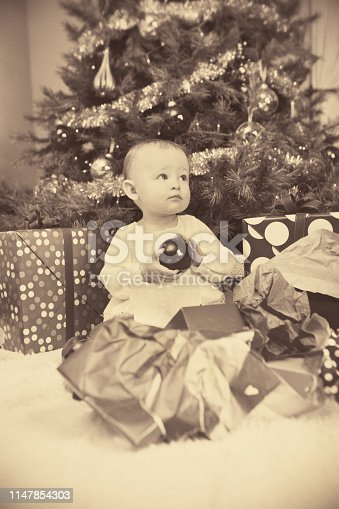 A vintage retro style photo in Sepia tone of a happy one year old Caucasian baby in front of a Christmas tree with presents.