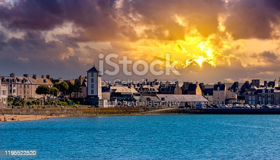 Saint-Malo, Brittany, France - May 31, 2019: Vintage architecture and beach with dramatic sunrise in background
