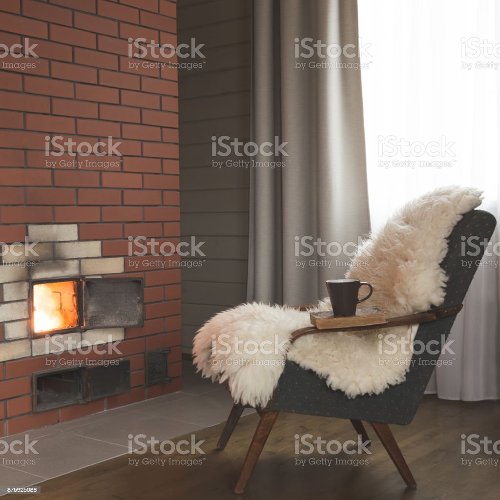 A vintage armchair covered with white furskin for pleasant reading and relaxation near the fireplace in dark interior. stock photo