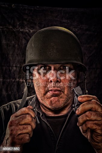 A Vintage Dazed Army Soldier pulling the pin of a pineapple hand grenade, looking at the camera