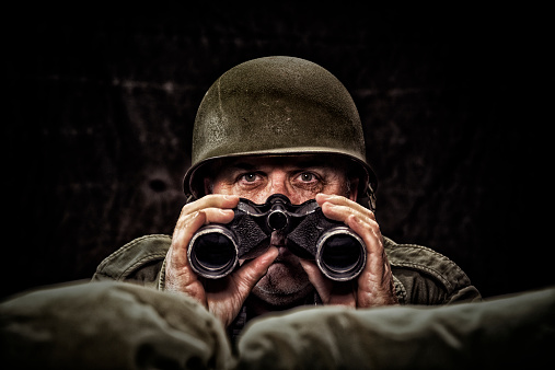 Vintage Army Soldier holding binoculars looking over the sand bags of his fox hole, with low key lighting
