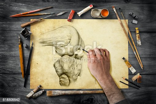 Drawing hand working on anatomic illustration. Vintage artist's equipment on wooden desk. Paint, brushes, pen and ink, pencil, eraser. XXXL (Canon Eos 1Ds Mark III)