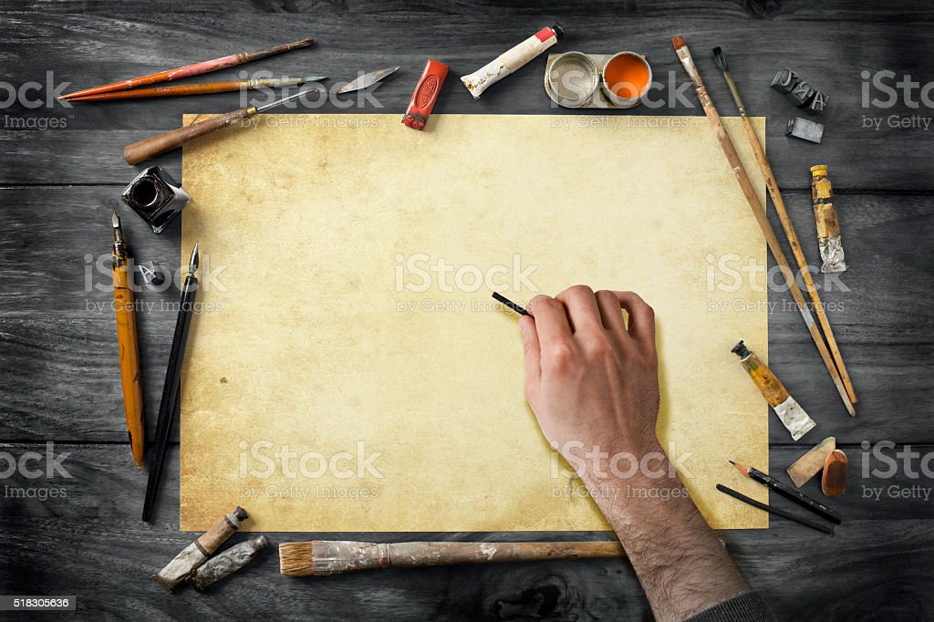 vintage artist's equipment on desk and drawing hand stock photo