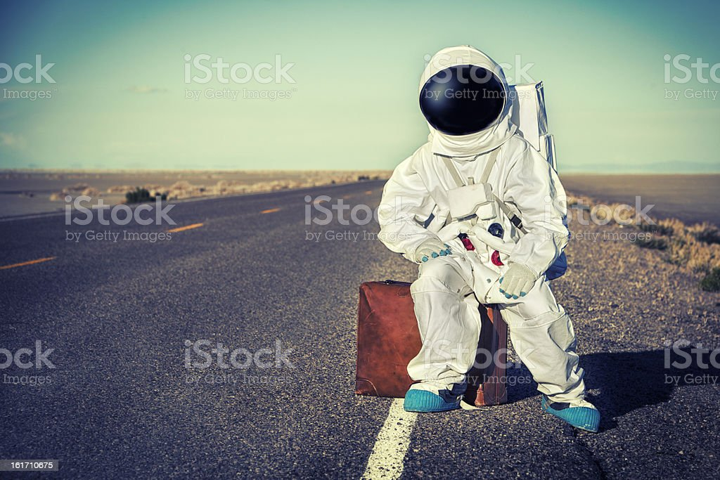 Vintage Astronaut Sitting On Luggage Waiting For A Ride stock photo