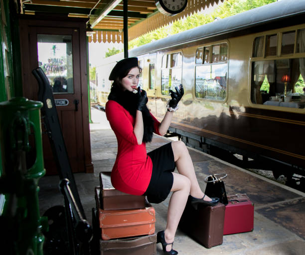 vintage attractive female wearing red dress and black beret, sitting on suitcases applying her makeup at train station stock photo