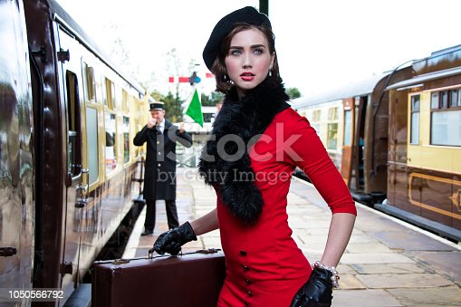 istock vintage attractive female wearing red dress and black beret with suitcases on platform of train station 1050566792