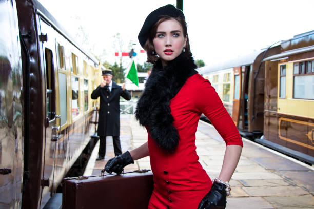 vintage attractive female wearing red dress and black beret with suitcases on platform of train station stock photo