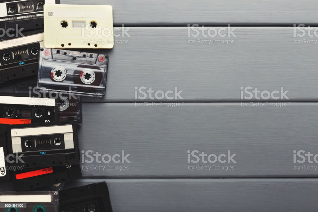 Creative border of vintage audio cassettes. Old retro tapes on gray...