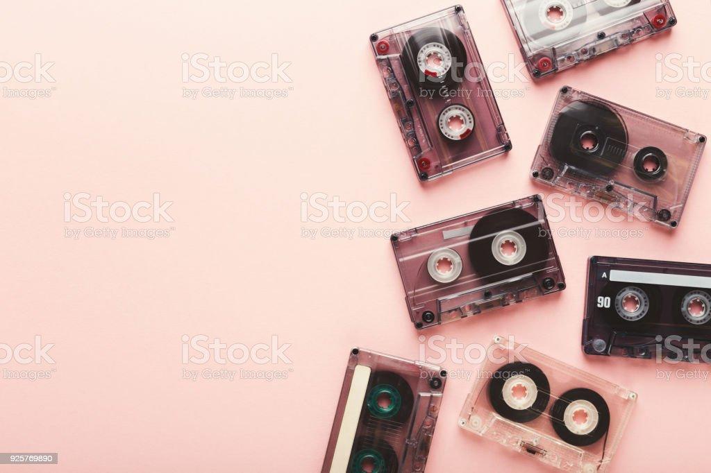 Vintage audio cassettes border on pink background stock photo