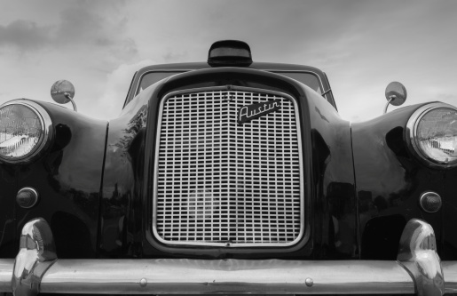 Perth, Western Australia - September 7, 2014: Black and White Austin FX4 London Taxi cab saloon with rounded mirrors.
