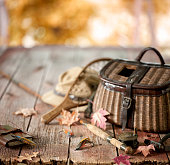 Vintage Wicker Creel and Fly Fishing Equipment Set against a Natural Autumn Scenic Background