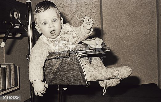 Vintage black and white image of a cute and surprised baby boy on a baby chair looking straight to camera .