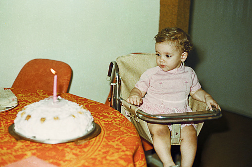 Vintage image from the seventies of a baby girl first birthday