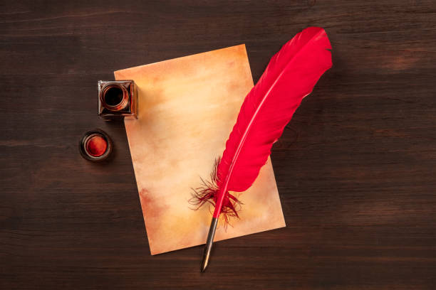 A vintage background with a vibrant red quill on a piece of old paper, with an ink well, on a dark wooden background with copy space stock photo