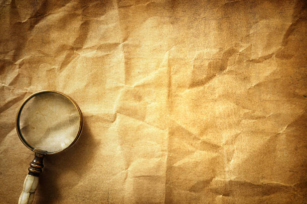Vintage background with magnifying glass Vintage magnifying glass on old parchment paper background detective stock pictures, royalty-free photos & images