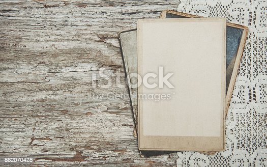 882302538 istock photo Vintage background with old photos on wood with lace 862070428
