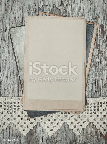882302538 istock photo Vintage background with old photos on wood with lace 862070560