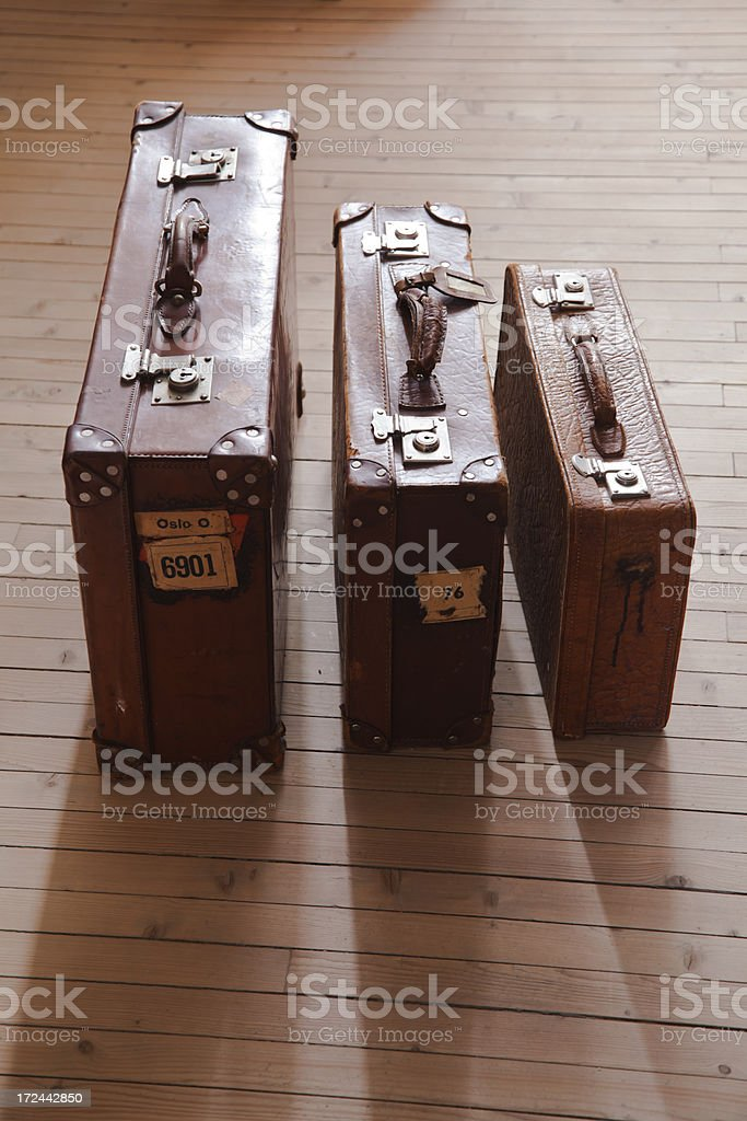 Vintage backlit  leather suitcases in a row on wooden floor. royalty-free stock photo