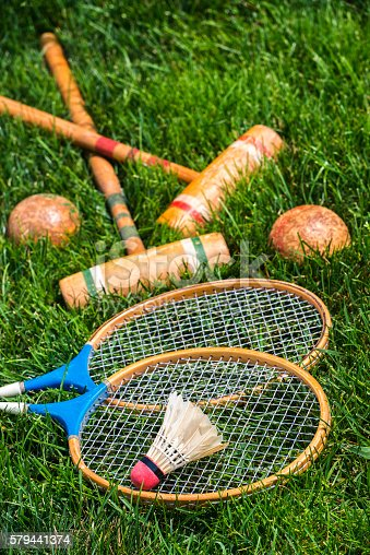 A pair of vintage wooden badminton rackets and a feathered shuttlecock lying in grass, along with a pair of croquet mallets and balls in the background. Great old fashion family fun games for all ages.