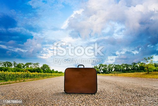 Vintage baggage thrown on the road. Conceptual shot journey, adventure, trip. Suitcase on the road in the field on the background of a beautiful sky with clouds. Auto stop vacation concept.