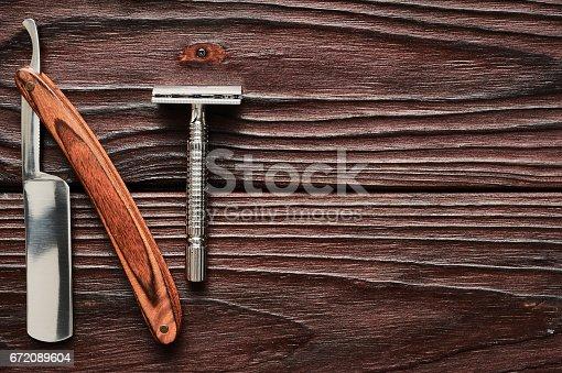 672089638 istock photo Vintage barber shop razor tools on wooden background 672089604