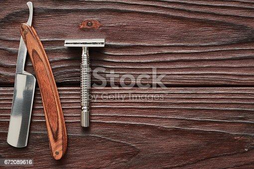 672089638 istock photo Vintage barber shop razor tools on wooden background 672089616