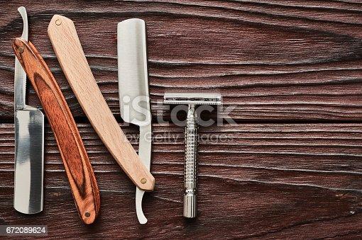 672089638 istock photo Vintage barber shop razor tools on wooden background 672089624