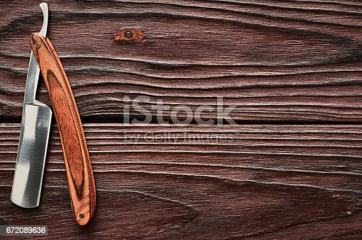 1126324804 istock photo Vintage barber shop straight razor tool on wooden background 672089636