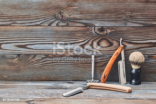 672088820 istock photo Vintage barber shop tools on wooden background 672040700