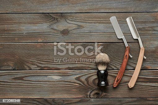 672088820 istock photo Vintage barber shop tools on wooden background 672085348