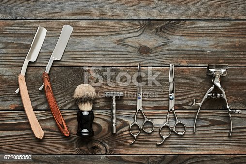 672088820 istock photo Vintage barber shop tools on wooden background 672085350